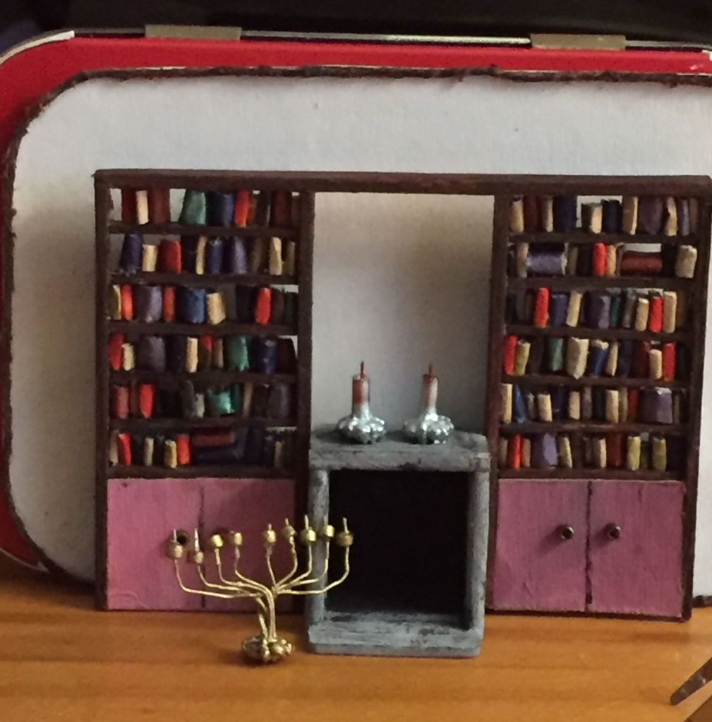 Miniature book cases, with books, a fireplace, two candlessticks, and on the floor, a miniature Menorah