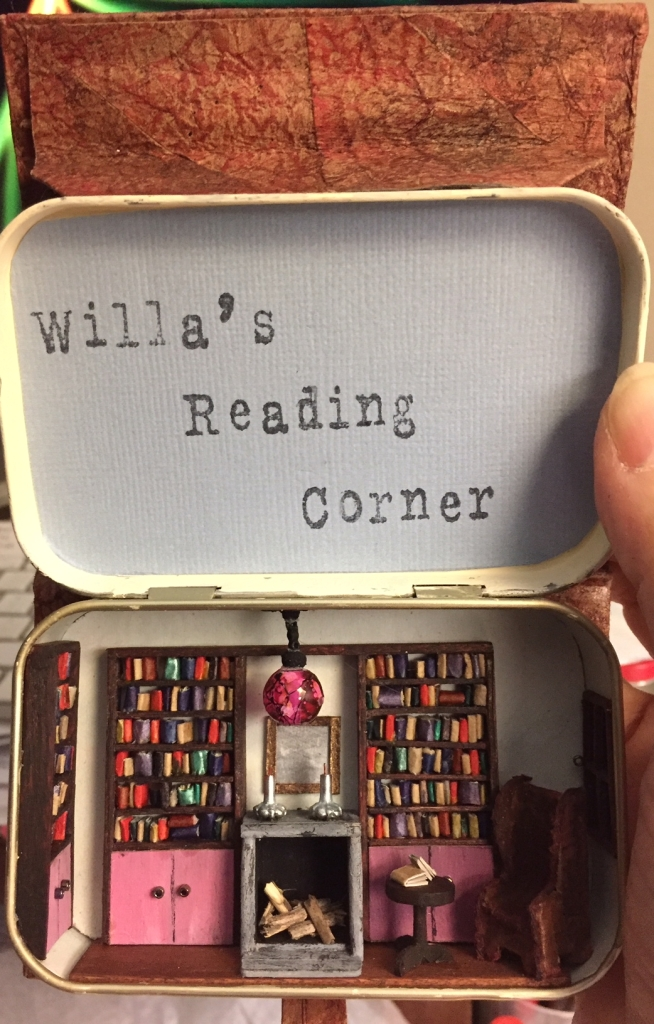 Head on shot of the open book/Altoids tin, showing a diorama of a tiny library with reading chair, fireplace, table, window, and bookcases full of books.