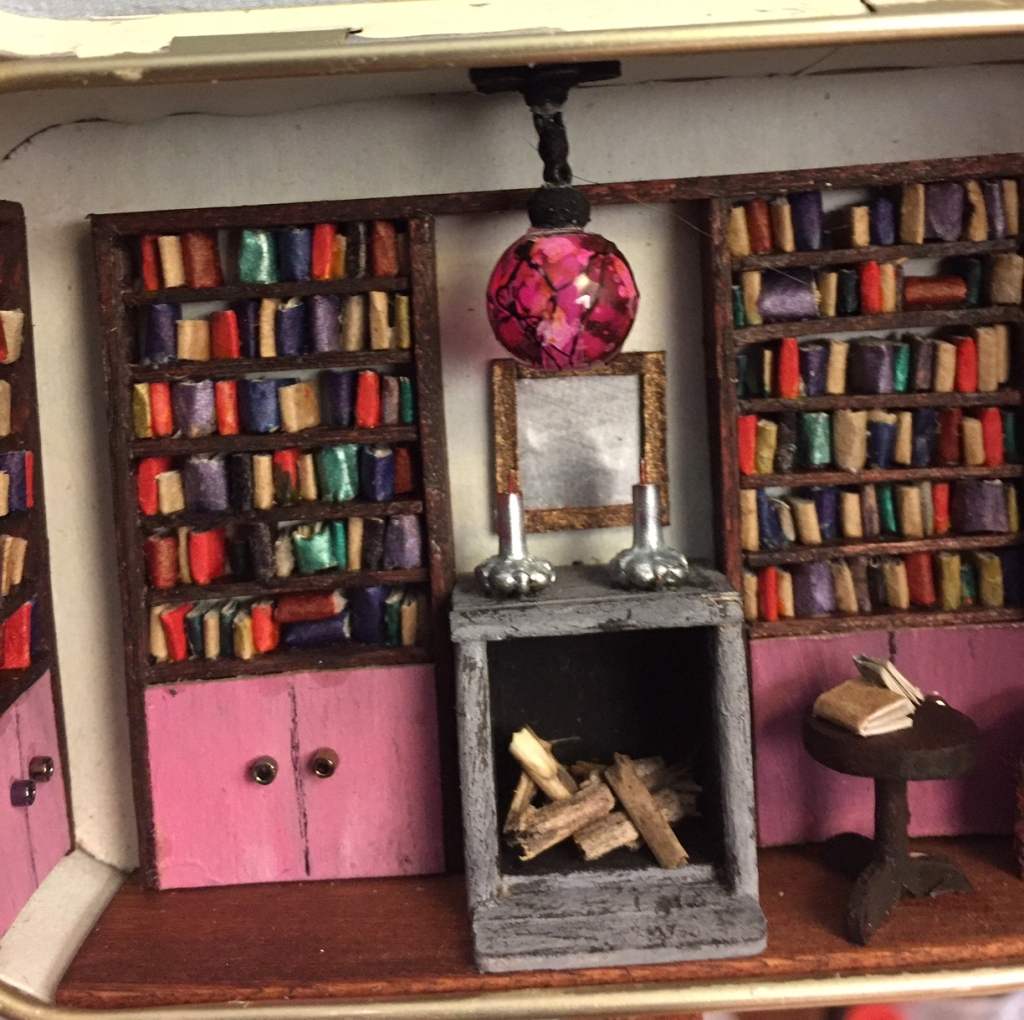 Close up of the inside of the Altoids tin, dressed up as a tiny library, showing the fireplace with two silver candlesticks, a mirror, with two bookcases on either side and a small round table with books.