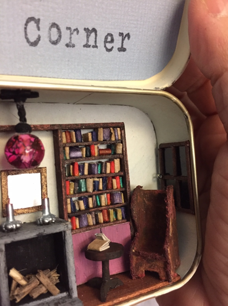 Close up of the inside of the tin, right side, showing the reading chair in front of a bookcase, with a simulated dark window behind it.