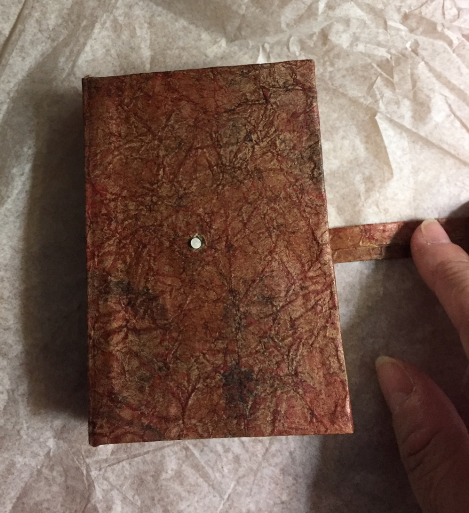 Holding the strap open, showing the tiny magnet embedded on the front cover of the 'book'
