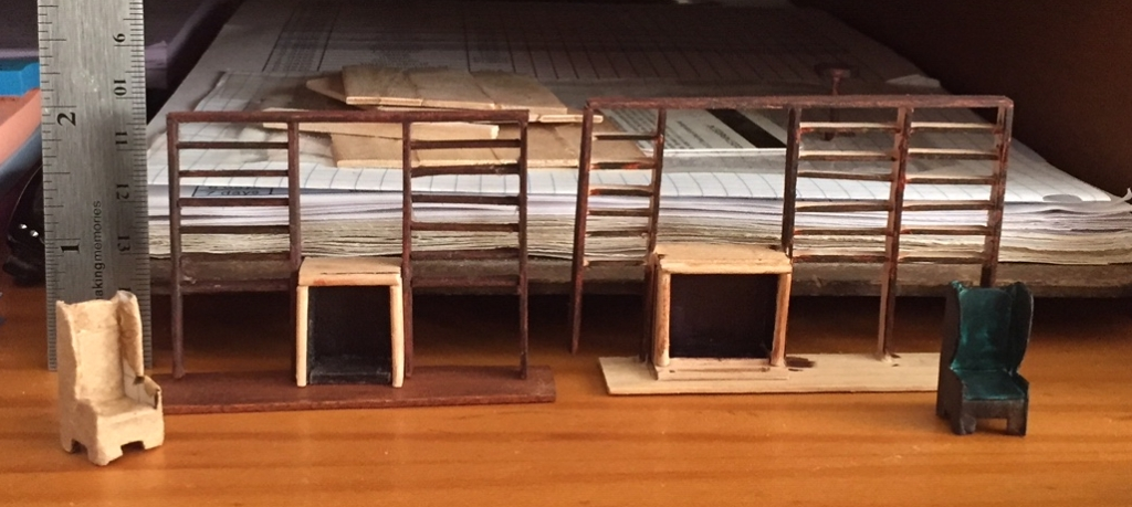 Two sets of tiny bookcases, still empty, displayed side by side. The one on the right is pretty crooked, the one on the left is square.