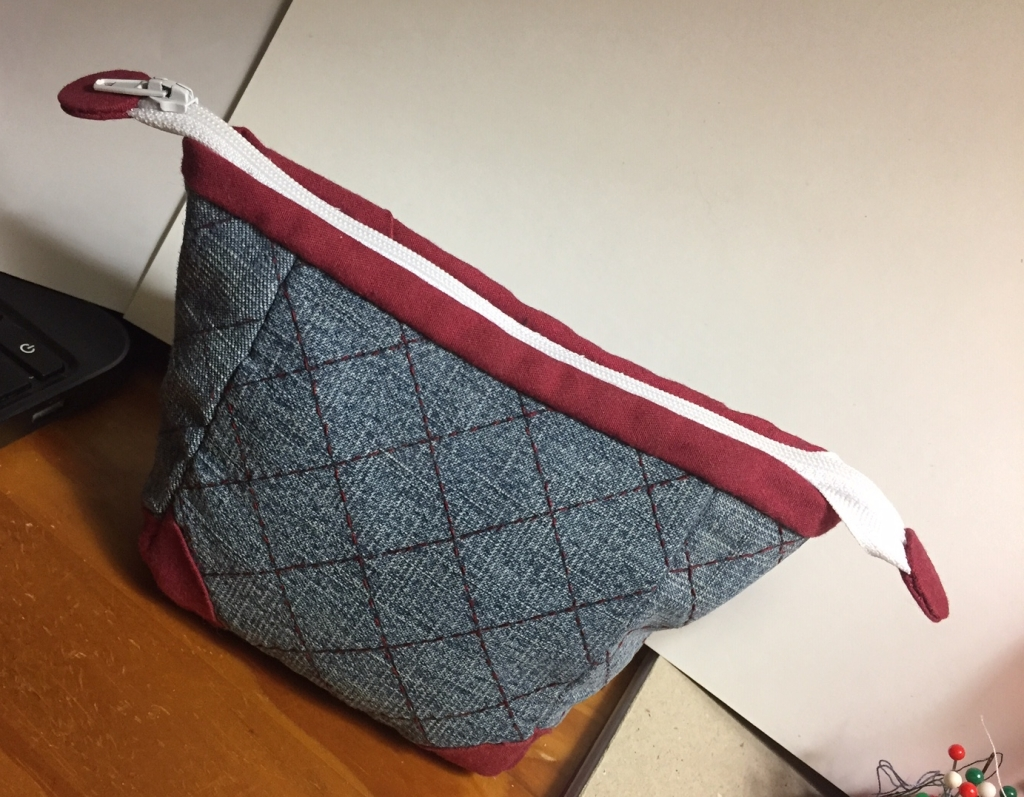 Denim pouch with white zipper and round zipper end caps in red